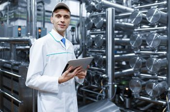 Technologist in a white coat makes the necessary entries in the tablet is at the factory. A man with a digital tablet in uniform in the production shop. interior of production department on background