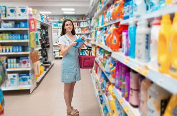 A young pretty woman chooses a cleaning agent in the store. Purchase and sale of goods in the store.