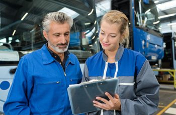 bus maintenance mechanic reading the clipboard