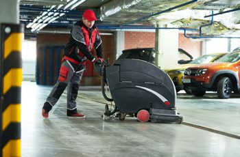 cleaning service. worker with machine cleaning floor in parking garage
